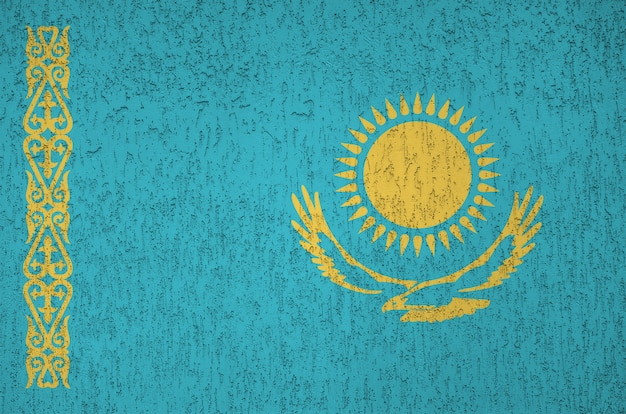 Kazakhstan flag depicted in bright paint colors on old relief plastering wall.