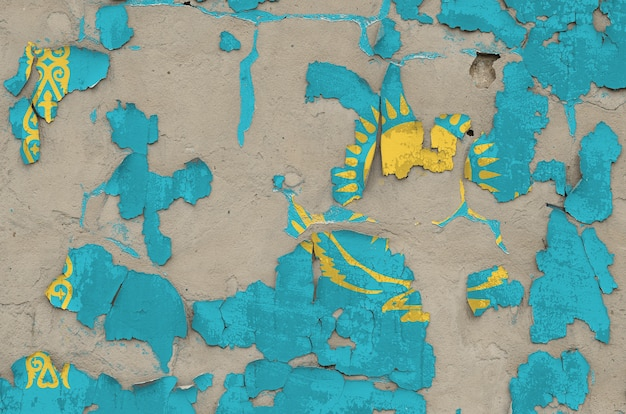Kazakhstan flag depicted in paint colors on old obsolete messy concrete wall closeup. textured banner on rough background