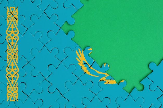 Kazakhstan flag  is depicted on a completed jigsaw puzzle with free green copy space on the right side