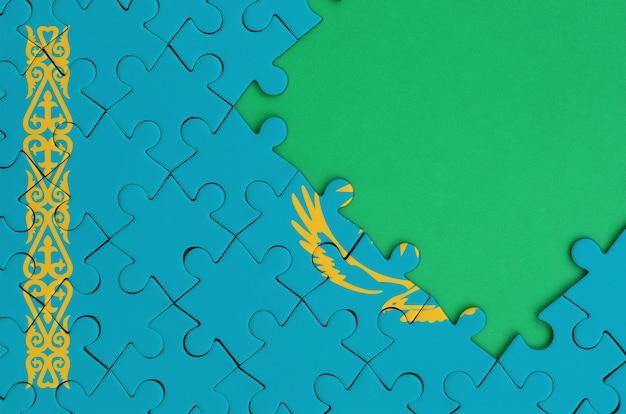 카자흐스탄 국기는 오른쪽에 무료 녹색 복사 공간이있는 완성 된 직소 퍼즐로 그려져 있습니다.