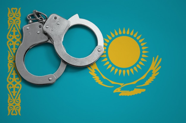 Kazakhstan flag  and police handcuffs. the concept of crime and offenses in the country