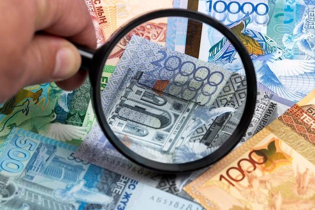 Казахстанский тенге в увеличительном стекле - деловой фон
