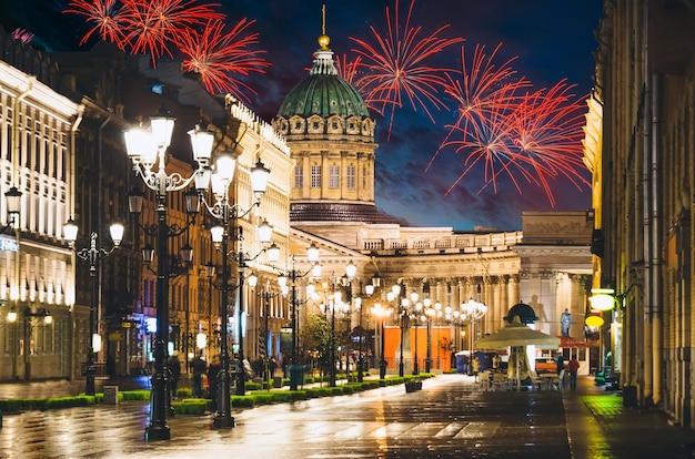 Казанский собор и невский проспект ночью освещают старые дома салютом на заднем плане в санкт-петербурге.