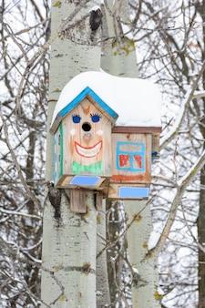 Казань, россия - 25 февраля 2019 г .: улыбающиеся скворечники. скворечник в виде забавной мордашки на дереве. деревянный скворечник ручной работы, покрытый снегом. зимний пейзаж с деревьями, покрытыми снегом.