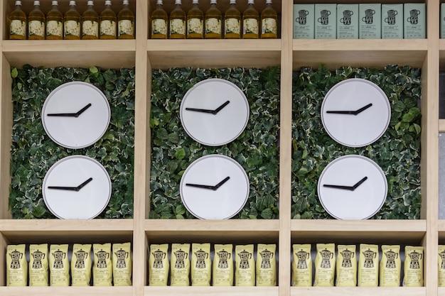 Казань / россия - 10 мая 2019 г .: витрина с интересными часами, сиропом и пакетами с кофе. много часов, много времени. интерьер.