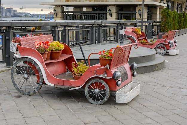 Казань, россия - 02 октября 2019 г .: старинные ретро-автомобили с цветами на кремлевской набережной в осенний пасмурный день. набережная реки казанки.