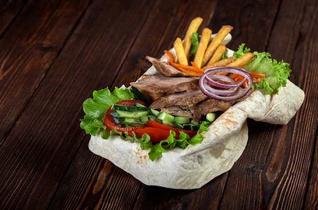 Kebab beef on lavash bread with sauce and vegetables