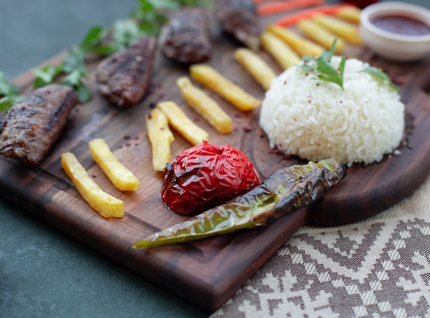 Kebab board with french fires, grilled foods and rice.
