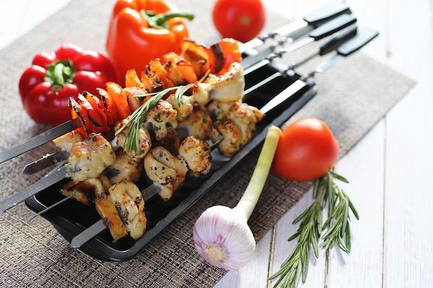 흰색 테이블에 야채와 함께 금속 꼬치에 구운 케밥