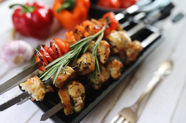 Шашлык, приготовленный на металлических шпажках с овощами, подается на белом столе