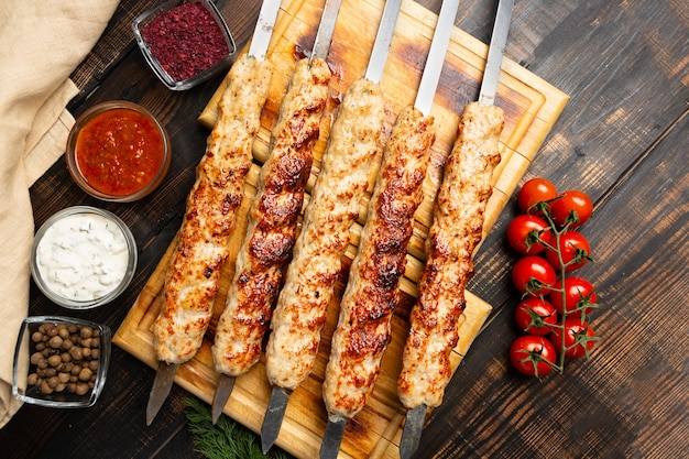 Kebab made of minced meat on metal skewer with vegetables and sauce on dark wooden