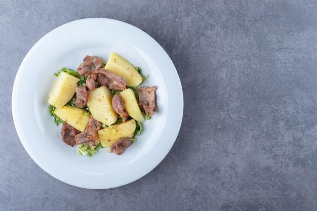 Кусочки шашлыка и отварной картофель на белой тарелке.