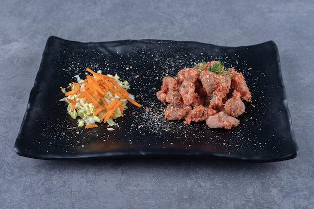 Кусочки шашлыка и салат на черной тарелке.