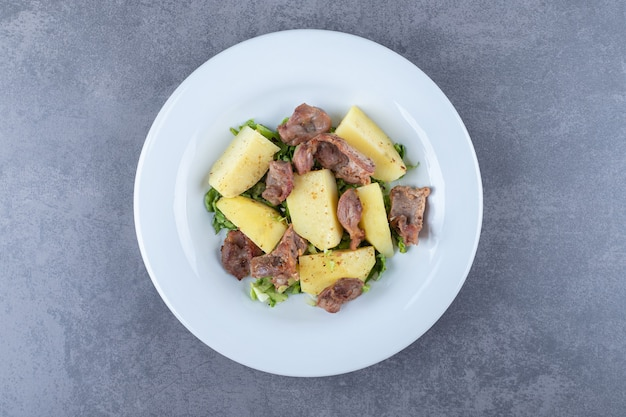 Kebab pieces and boiled potatoes on white plate.