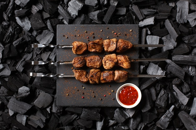 Kebab on skewers. three portions of grilled meat on a stone plate. charcoal background. top view.