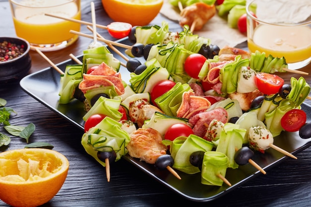 Kebab on skewers with chicken meat, zucchini, tomatoes, mozzarella balls, salami slices, olives on a black plate on a wooden table with fresh orange juice in glass cups, summer picnic recipe, close-up