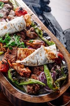 Kebab varieties with vegetables inside wooden platter.