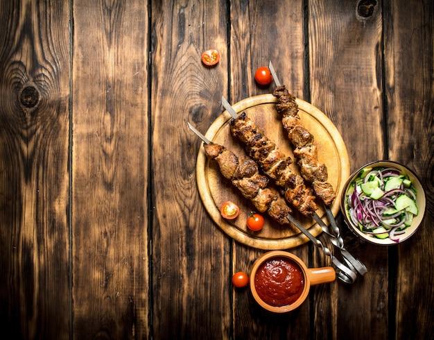 오이와 양파의 신선한 샐러드와 케밥. 나무 배경.