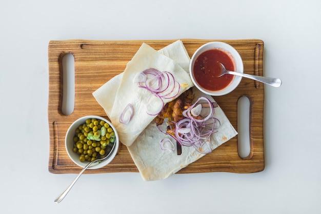 완두콩, 양파, 피타 빵에 빨간 소스를 곁들인 케밥. 평면도.