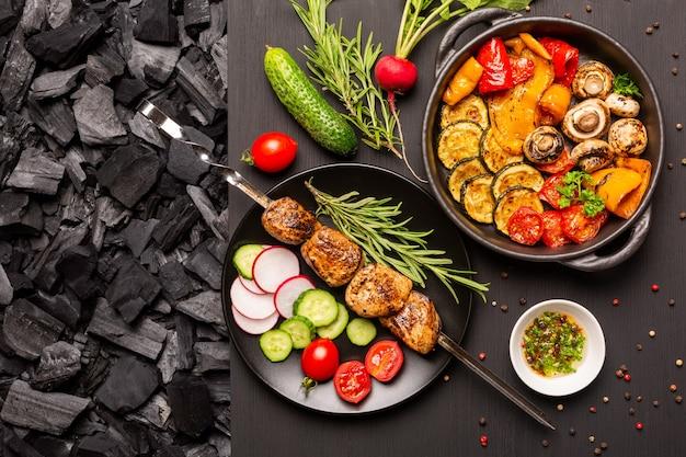 검은 나무 탁상 위에 구운 야채와 함께 접시 팬에 야채와 케밥