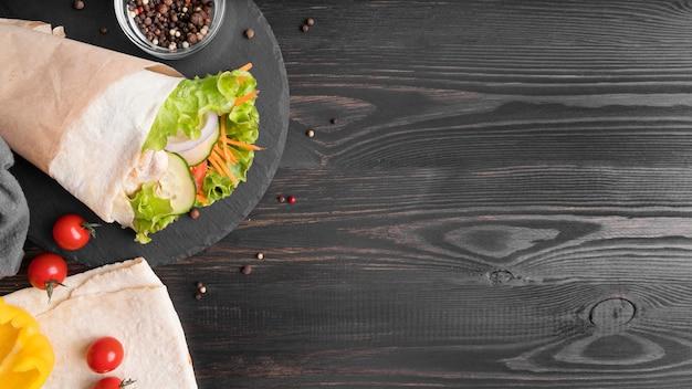 Ролл из кебаба с мясом и овощами на тарелке