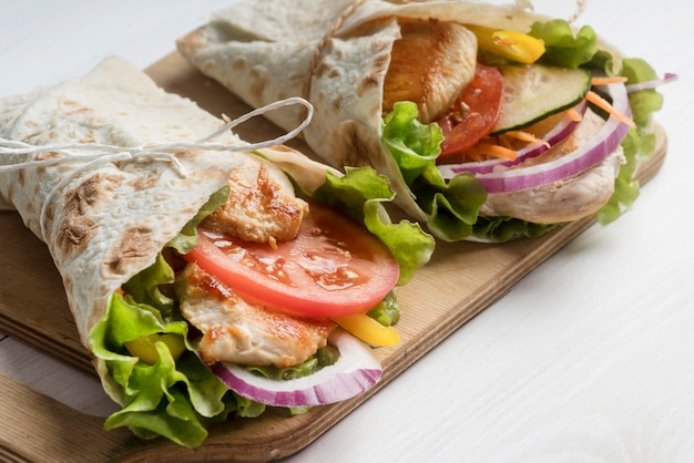 Kebab wrap with meat and vegetables on wooden board
