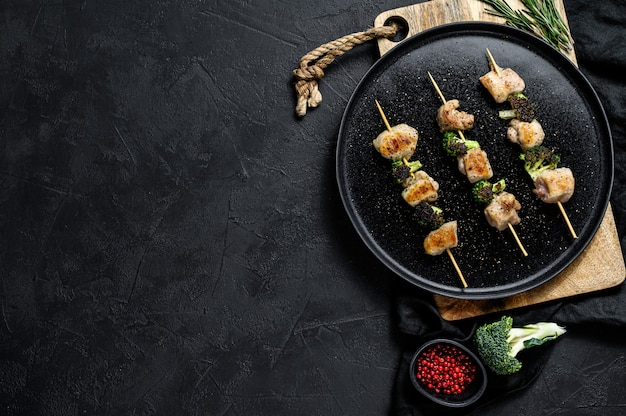 Kebabs - grilled meat skewers, shish kebab with vegetables. black background. top view. space for text