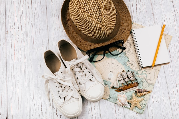 Keds, hat, glasses, notebook, little wooden ship lie on white travel map
