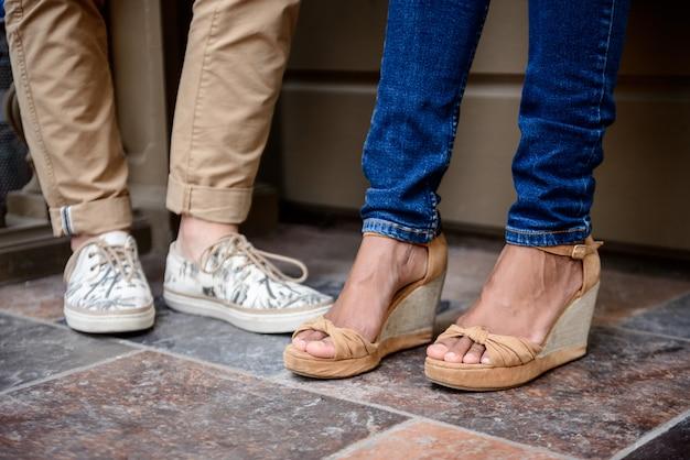Закройте вверх ног пары в keds стоя на улице.