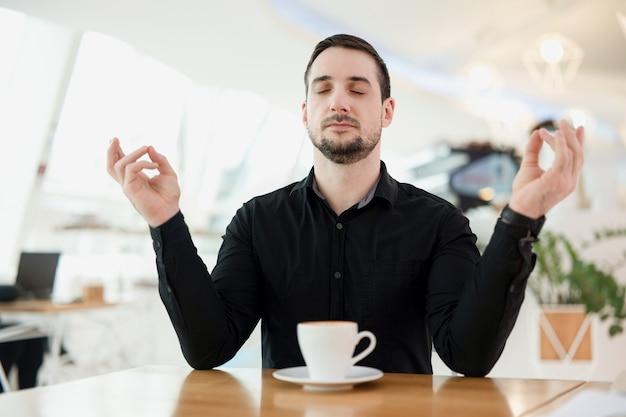落ち着いて、おいしいエスプレッソを一杯飲みましょう。カフェインが大量にあるためにパニック発作を起こしたため、男性は瞑想しています。背景のコーヒーショップ。スタイリッシュな男。