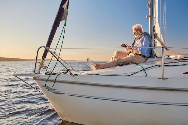 Сохраняйте спокойствие и расслабьтесь, вид сбоку на пожилого мужчину, сидящего на борту парусной лодки или яхты, плавающей в