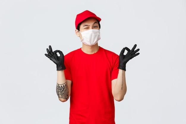 落ち着いて私たちの配送会社に頼ってください。赤い帽子とtシャツを着た陽気でリラックスしたアジアの配達人、禅、ニルヴァーナのジェスチャー、ウインクを見せて、パッケージの安全を保証します。宅配便は平和を保つ