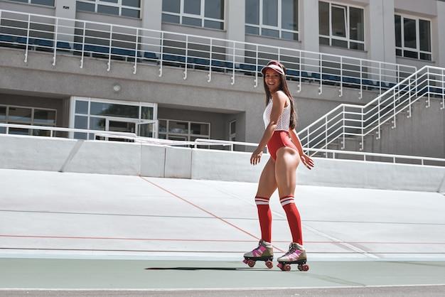 Сохраняйте спокойствие и катайтесь на коньках на красивой женщине, катающейся на роликах в скейтпарке, улыбаясь и глядя
