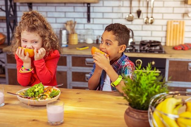 침착하십시오. 저녁 식사를 즐기면서 친구를 응시하는 세심한 국제 어린이