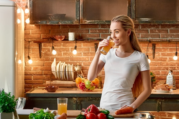 Сохраняйте спокойствие, ешьте фрукты и овощи, счастливая молодая женщина готовит овощи на современной уютной кухне
