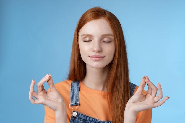 Mantieni la calma rossa ragazza rilassata rimanere sollevata positiva chiudere gli occhi sorridendo felice alzando le mani lateralmente loto mudra gesto pratica meditazione yoga fare esercizio di respirazione, sfondo blu.