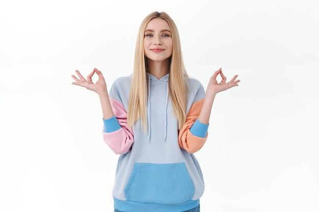 Mantieni la calma e fai shopping online. una ragazza bionda pacifica, felice e sollevata, si tiene per mano in un gesto zen, sorride compiaciuta, sente pazienza e pace