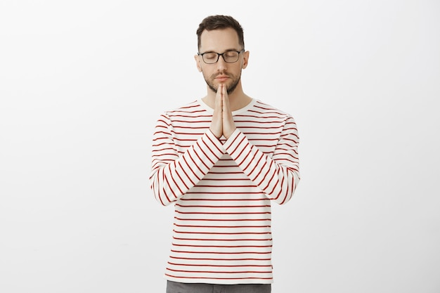 Keep feelings under control. portrait of focused calm handsome adult father in stylish glasses and striped shirt, holding hands in pray, closing eyes and praying or hoping, wishing god will hear him