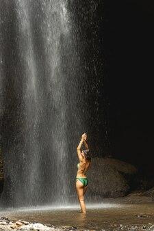 건강을 유지하십시오. 물 속에 서서 튀는 폭포, 관광 개념을 즐기는 매력적인 여성