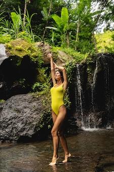 健康を保ちます。水中に立って、カメラでポーズをとっている間、両腕を上げる美少女