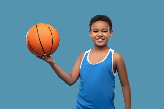 건강 유지. 그의 손가락에 오렌지 큰 공을 들고 스포츠 블루 셔츠에 아프리카 계 미국인 소년 미소