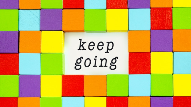 Keep going typed on white paper surrounded by colourful blocks in a conceptual image of inspiration and motivation.
