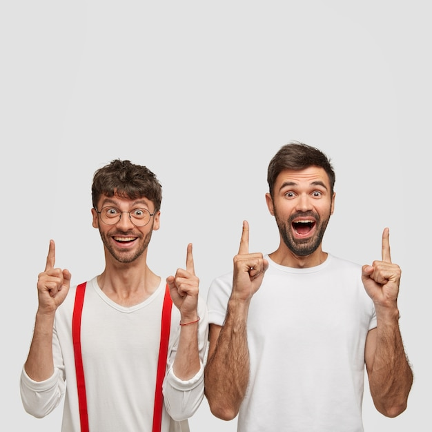 Keep heads up! optimistic unshaven brothers point with both index fingers, smile broadly while show new banner, dressed in white clothes, isolated over  wall, demonstrate new amazing product