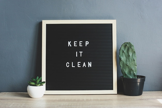 Keep it clean quote on blackboard with cactus and succulent on wooden table