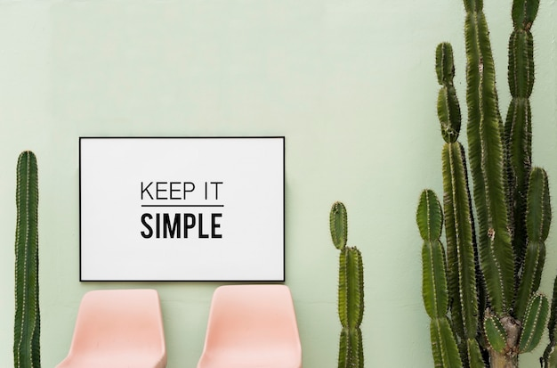 Keep it simple in white frame hanging on green wall