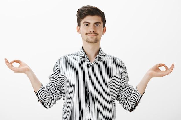 요가로 몸과 마음을 건강하게 유지하십시오. 수염과 콧수염이있는 차분한 긍정적 인 남자, 선 제스처로 손을 펴고 편안한 표정으로 웃고, 회색 벽 위로 명상을 마무리