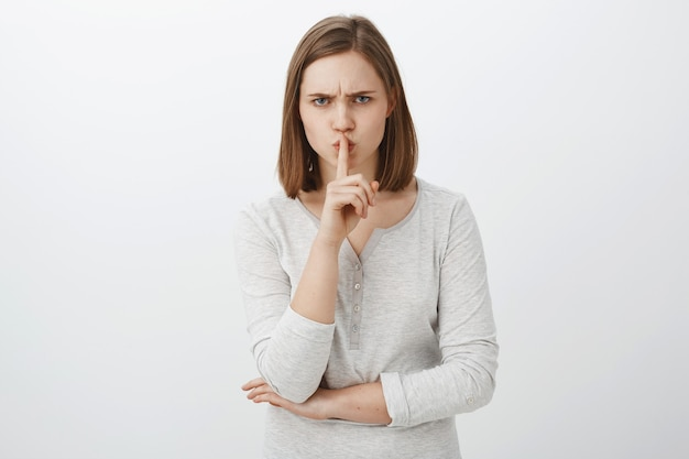 Keep mouth shut i prohibit tell anyone my secret. portrait of serious-looking irritated bossy girl with brown hair frowning shushing with index finger over mouth demanding keep quiet