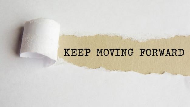 前進し続ける。言葉。破れた紙の背景に灰色の紙のテキスト。