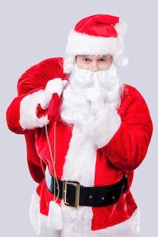 私の秘密を守ってください!プレゼントと袋を運び、灰色の背景に立っている間、唇に指を保持している伝統的なサンタクロースの肖像画