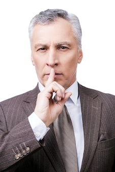 Keep my secret!  serious mature man in formalwear holding finger on lips and looking at camera while standing against white background